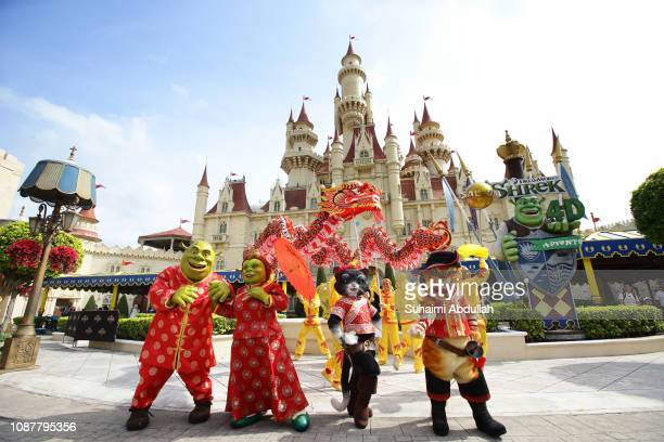 Shrek and Fiona characters from the movie Shrek and 'Puss in Boots' join in a dragon dance procession at Universal Studios Singapore at Resorts World...