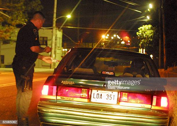 Shreveport Police Officer Cpl Will Bates makes a late night traffic stop as the driver hands officer Bates his drivers license January 25 2005 in...