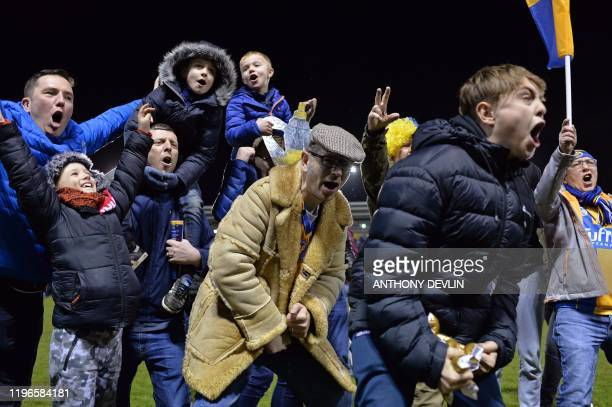 Shrewsbury fans celebrate on the pitch after the final whistle in the English FA Cup fourth round football match between between Shrewsbury Town and...