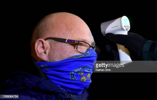 Shrewsbury Town fan has their temperature taken whilst wearing a face mask ahead of the Sky Bet League One match between Shrewsbury Town and...