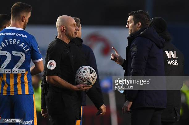 Shrewsbury Town's English manager Sam Ricketts gestures as he talks with referee Roger East following the English FA Cup fourth round football match...
