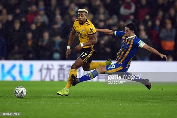 Shrewsbury Town's English midfielder Oliver Norburn fouls Wolverhampton Wanderers' Spanish striker Adama Traore and then receives a yellow card...