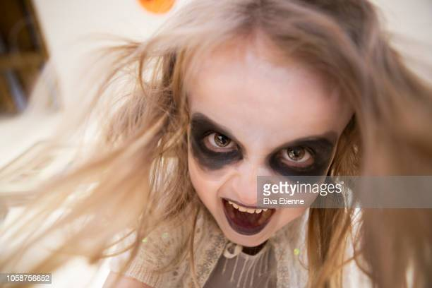 Shrieking girl (6-7) with long tangled hair and Halloween face paints from directly below