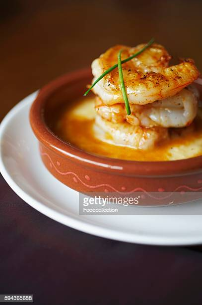shrimp and grits in a brown dish with chive garnish - shrimp and grits stock photos and pictures
