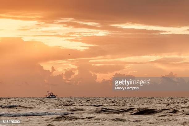a shrimp boat at sunrise in the gulf of mexico - texas gulf coast stock photos and pictures