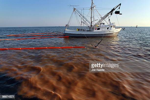 A shrimp boat passes through a heavy oil slick as it uses the deployed oil boom and absorption pads to collect the oil from the massive spill on May...