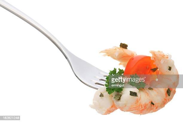 Crevettes, persil et tomate sur une fourchette isolée