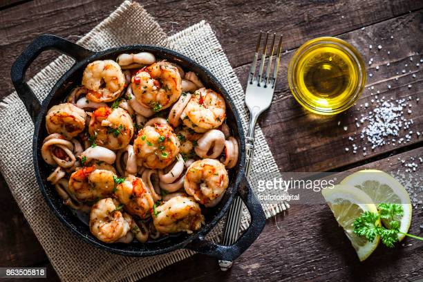shrimps and calamari rings cooked on iron cast pan - seafood stock pictures, royalty-free photos & images