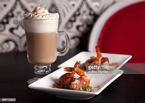 Shrimps with bacon on plates and cocktail in glass