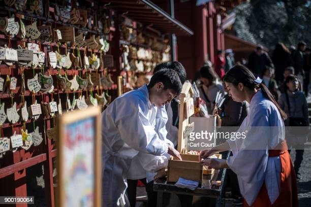 Shrine assistants prepare 'Ema' wooden plaques on which Shinto worshippers write prayers or wishes for new year visitors at Tsurugaoka Hachimangu...