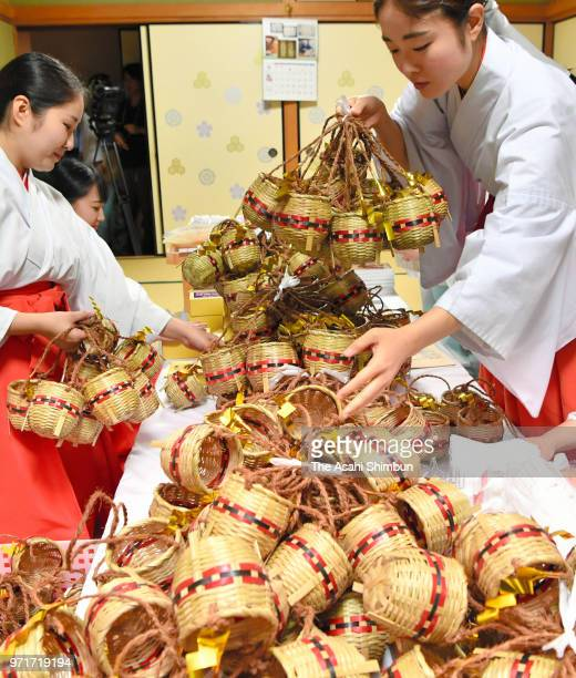 Shrine maidens pack the 'Oshioi' sand into the 'Tebo' baskets which will be used to purify the bodies of participants of Hakata Gion Yamakasa at...