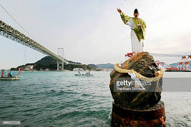 A Shrine priest of Akama Jinja Shrine stands on the sacred rock as a part of Shimenawa matsuri traditional ritual carried out on the shore of...
