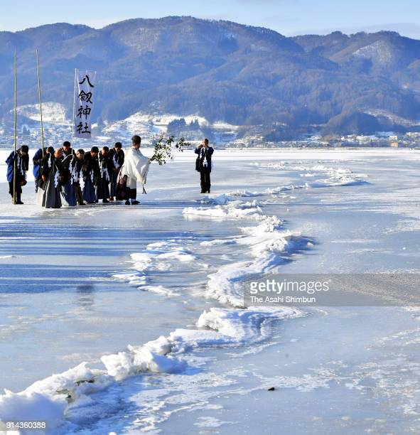 Shrine priest of Yatsurugi Jinja Shrine holds a ritual in front of the 'Omiwatari', natural phenomenon 'ice pressure ridging', on the fronze Lake...