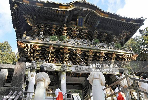 Shrine priests and maidens clean the Yomeimon Gate of the Nikko Toshogu Shrine on December 20 2011 in Nikko Tochigi Japan