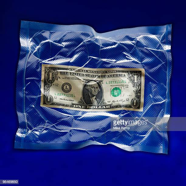 shrink wrapped dollar bill - airtight stock photos and pictures
