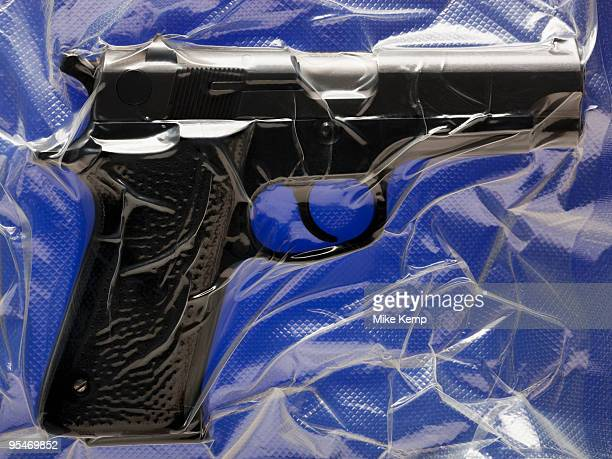 shrink wrapped hand gun - gun control stock pictures, royalty-free photos & images