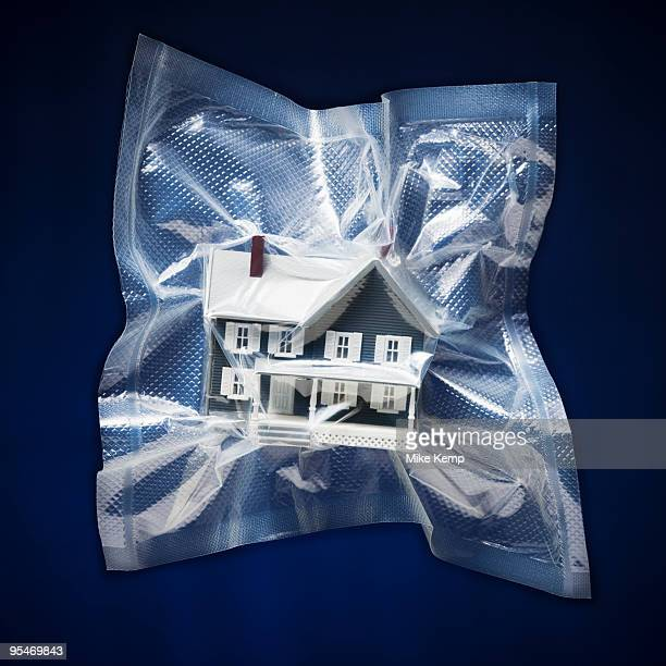 shrink wrapped toy house - airtight stock photos and pictures