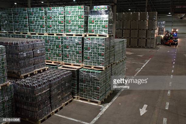 Shrinkwrapped cases containing bottles of Heineken lager sit on wooden pallets as a forklift truck is operated inside the warehouse at the Heineken...