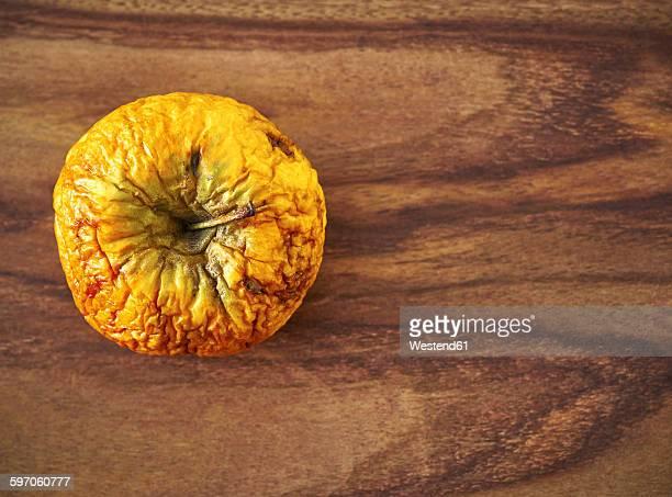 Shrivelled apple on grained wood