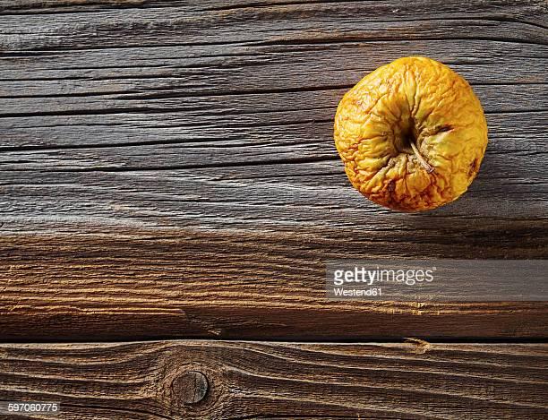 Shrivelled apple on rough wood