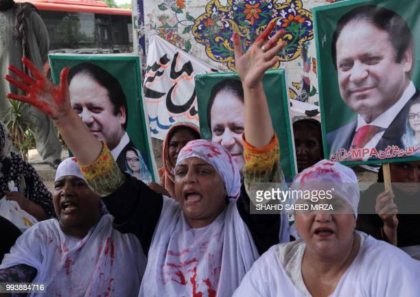 Shroud wearing activists of the Pakistan Muslim LeagueNawaz party shout slogans as they take part in a protest in Multan on July 8 after a sentencing...