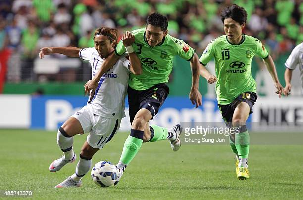 Shu Kurata of Gamba Osaka compete for the ball with Kim HyungIl of Jeonbuk Hyundai Motors during the AFC Champions League quarter final match between...