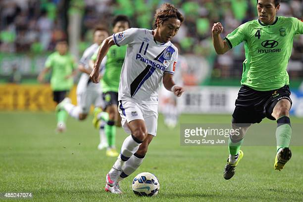 Shu Kurata of Gamba Osaka compete for the ball with Kim KeeHee of Jeonbuk Hyundai Motors during the AFC Champions League quarter final match between...