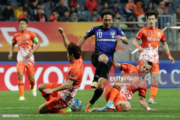 Shu Kurata of Gamba Osaka competes for the ball with Toscano Marcelo of Jeju United FC during the AFC Champions League Group H match between Jeju...