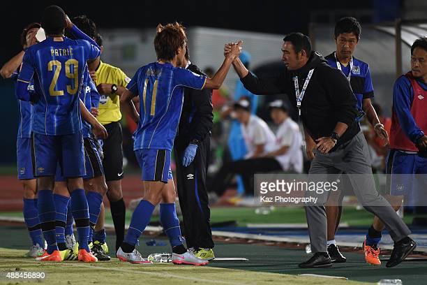 Shu Kurata of Gamba Oska, who scored the second goal shakes hands with Kenta Hasegawa, coach of Gamba Oska during the AFC Champions League quarter...
