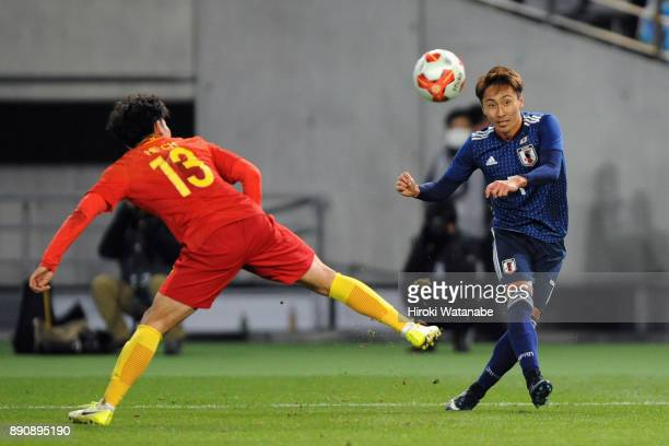 Shu Kurata of Japan and He Chao of China compete for the ball during the EAFF E1 Men's Football Championship between Japan and China at Ajinomoto...