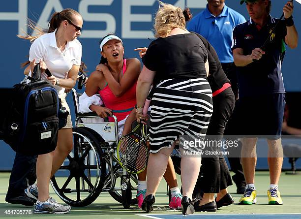 Shuai Peng of China is taken off the court by wheelchair after withdrawing from her women's singles semifinal match due to injury against Caroline...