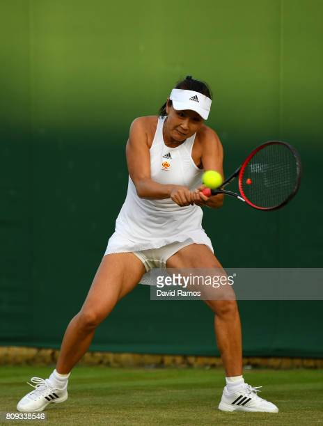 Shuai Peng of China plays a backhand during the Ladies Singles second round match against Carla Suarez Navarro of Spain on day three of the Wimbledon...