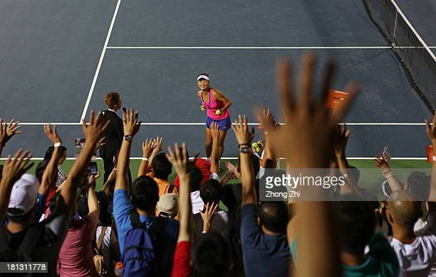 Shuai Peng of China throws gifts to fans with her partner SuWei Hsieh of Chinese Taipei after winning the doubles semi final of WTA Guangzhou Open...