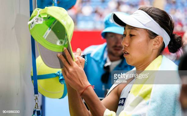 Shuai Zhang of China signs autographs after her victory in her first round match against Sloane Stephens of USA on day one of the 2018 Australian...