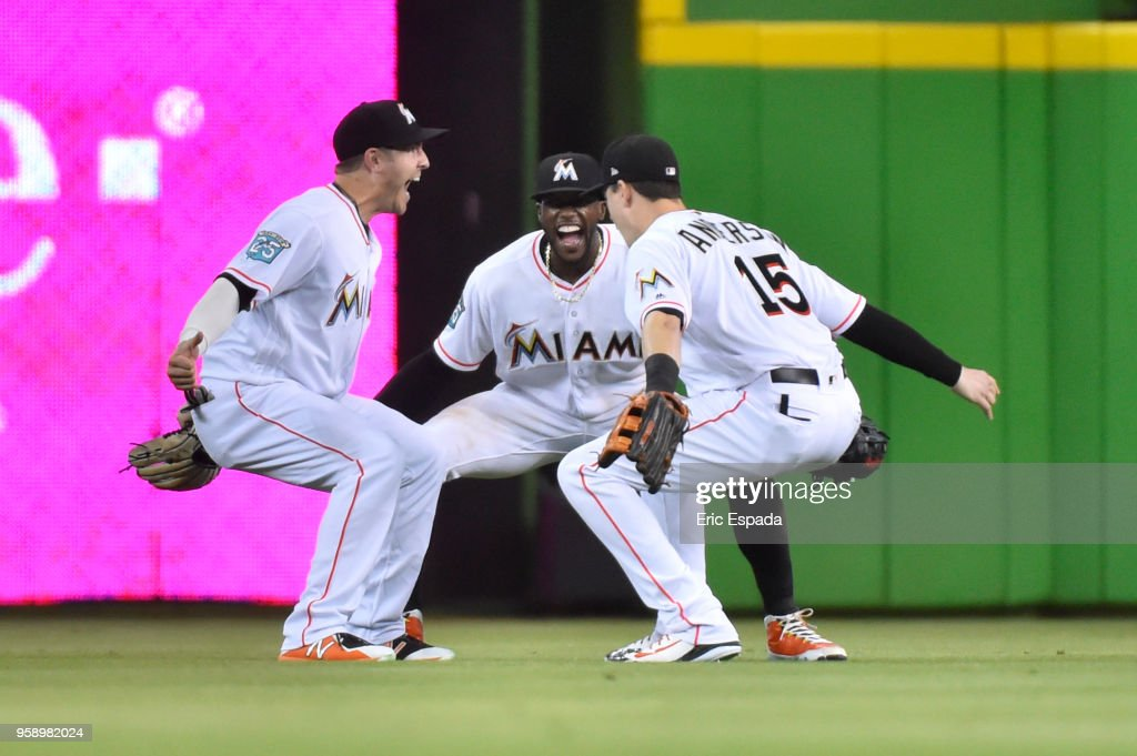 J.B. Shuck #3, Cameron Maybin #1 and Brian Anderson #15 of the Miami Marlins celebrate after defeating the Los Angeles Dodgers at Marlins Park on May 15, 2018 in Miami, Florida.