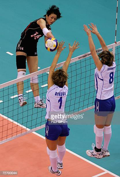 Shuka Oyama of Japan spikes the ball past Natalya Rykova and Korinna Ishimtseva of Kazakhstan during the Women's Team Tournament Preliminary Pool B...