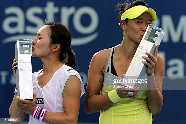 Shuko Aoyama of Japan and Kai-Chen Chang of Chinese Taipei kiss their trophies during a presentation ceremony after they defeated Janette Husarove of...