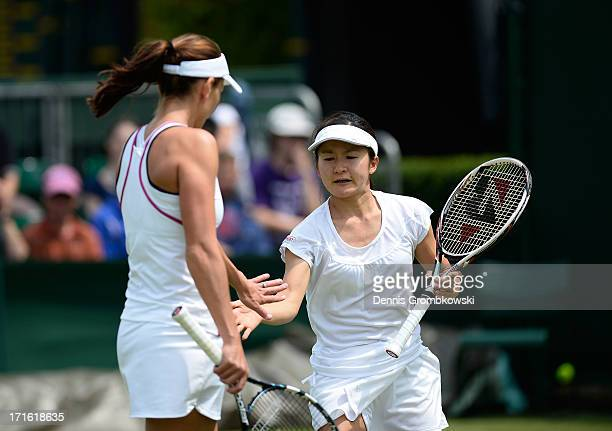 Shuko Aoyama of Japan taps hands with teammate Chanelle Scheepers of South Africa during the Ladies' Doubles first round match between Anastasia...
