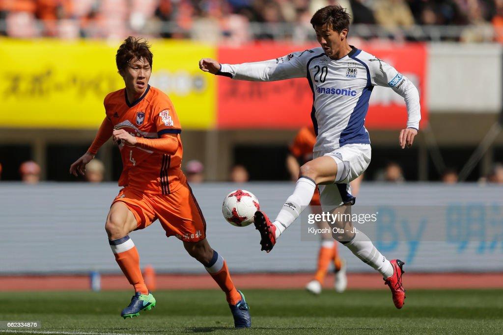 Shun Nagasawa of Gamba Osaka and Song Ju Hun of Albirex Niigata compete for the ball during the J.League J1 match between Albirex Niigata and Gamba Osaka at Denka Big Swan Stadium on April 1, 2017 in Niigata, Japan.