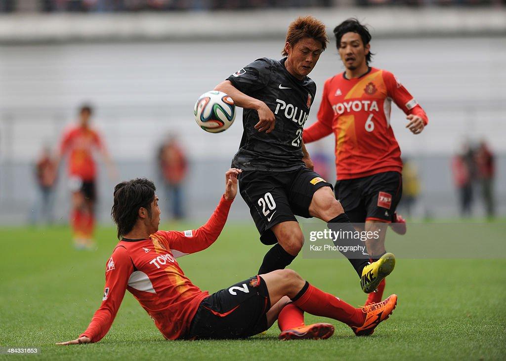 Shun Obu (L) of Nagoya Grampus challenges Tadanari Lee of Urawa Red Diamonds during the J. League match between Nagoya Grampus and Urawa Red Diamonds at the Toyota Stadium on April 12, 2014 in Toyota, Japan.
