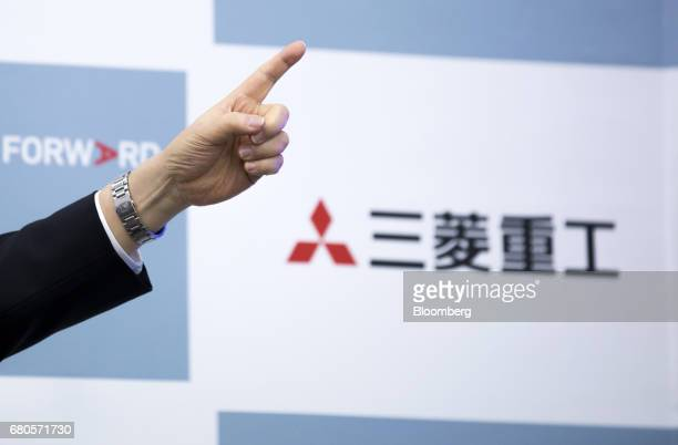Shunichi Miyanaga, president and chief executive officer of Mitsubishi Heavy Industries Ltd., points as he speaks in front of the company's logo...