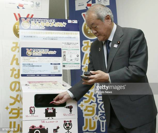 Shunichi Suzuki minister in charge of the 2020 Tokyo Olympic and Paralympic Games puts mobile phones in a box to collect unwanted digital devices set...