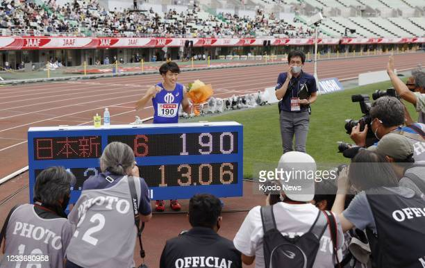 Shunsuke Izumiya poses for photos after setting a national record in the men's 110-meter hurdles and qualifying for the Tokyo Olympics at the...