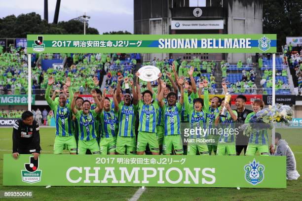 Shunsuke Kikuchi of Shonan Bellmare lifts the trophy as they celebrate the J2 Champions and promotion to the J1 after the J.League J2 match between...