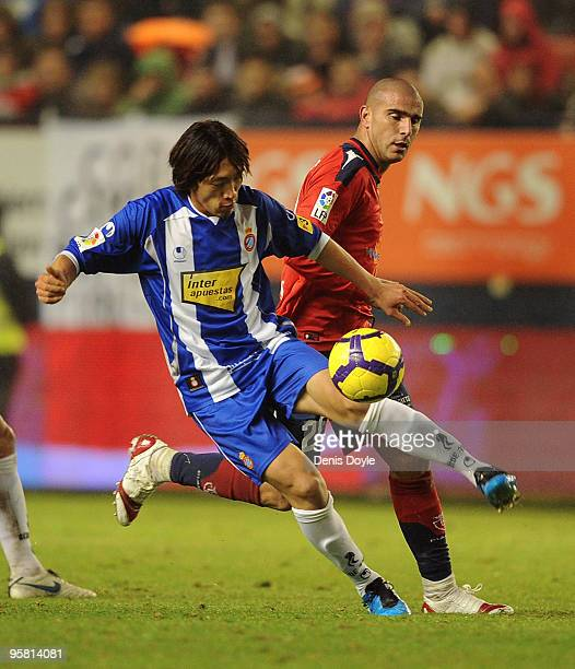 Shunsuke Nakamura of Espanyol beats Carlos Aranda of Osasuna to the ball during the La Liga match between Espanyol and CA Osasuna at the Reyno de...
