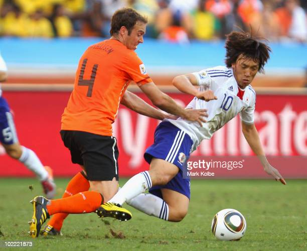 Shunsuke Nakamura of Japan falls under the challenge of Joris Mathijsen of the Netherlands during the 2010 FIFA World Cup South Africa Group E match...