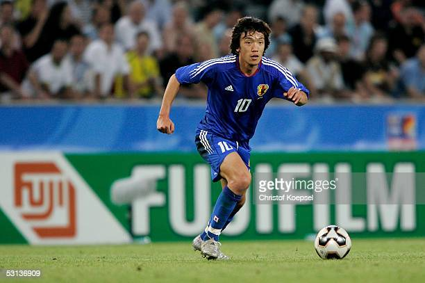 Shunsuke Nakamura of Japan runs with the ball during the match between Japan and Brazil for the Confederations Cup 2005 at the RheinEnergie Stadium...