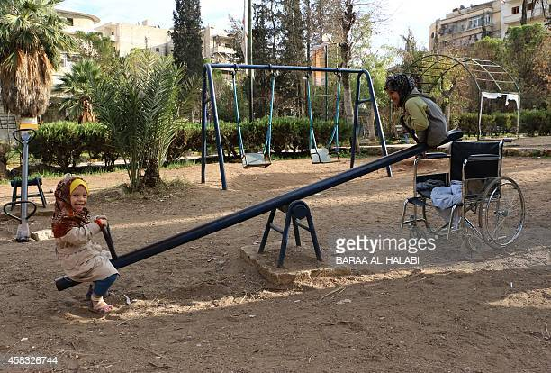 Shuruq a nineyear old Syrian girl who lost her legs after a shell hit her house plays on a seesaw with another child in a park in the northern Syrian...