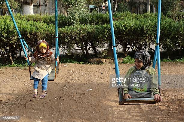 Shuruq a nineyear old Syrian girl who lost her legs after a shell hit her house plays on a swing with another child in a park in the northern Syrian...