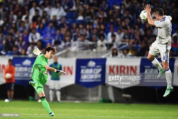 Shusaku Nishikawa of Japan kicks the ball while Armin Hodzic of Bosnia and Herzegovina blocks with his hand during the international friendly match...